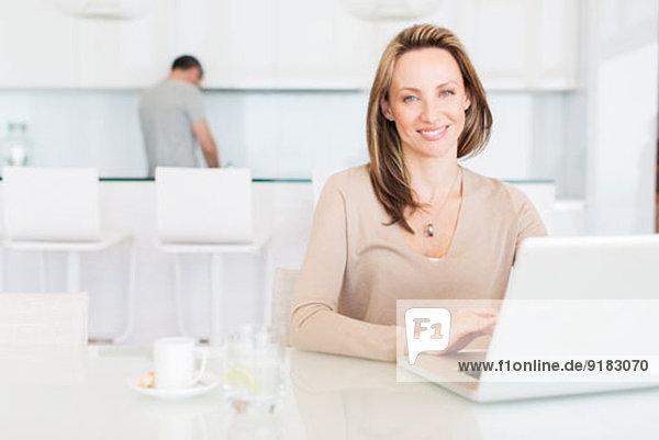 Frau mit Laptop am Frühstückstisch