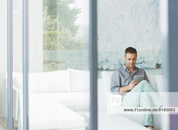 Mann mit digitalem Tablett auf dem Sofa