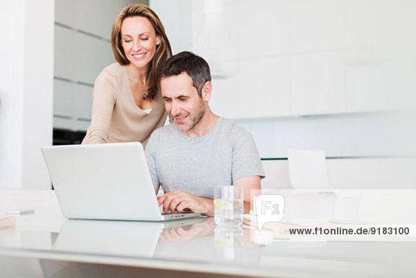 Paar mit Laptop am Frühstückstisch
