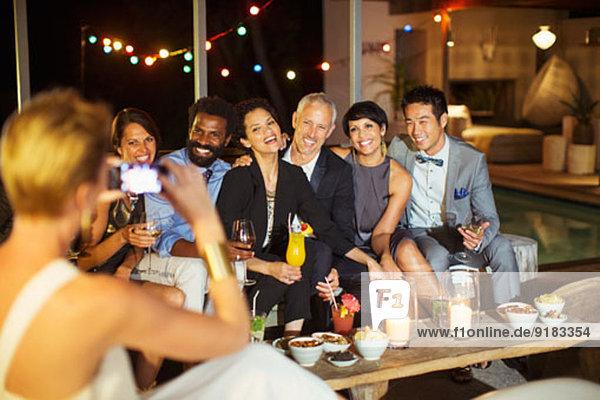 Frau beim Fotografieren von Freunden auf der Party