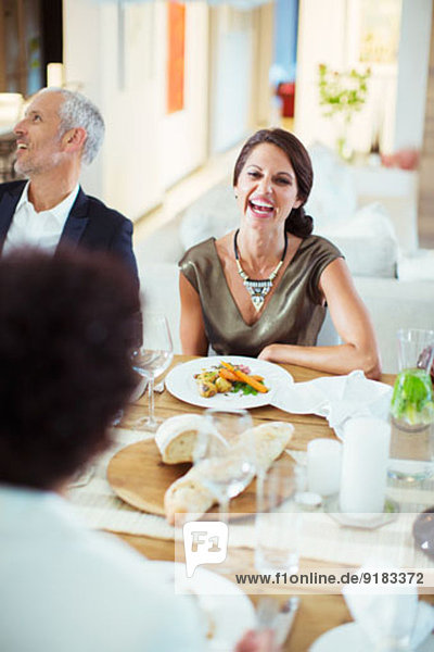 Woman laughing at dinner party