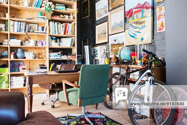 Schreibtisch  Bücherregale und Fahrrad im Arbeitszimmer