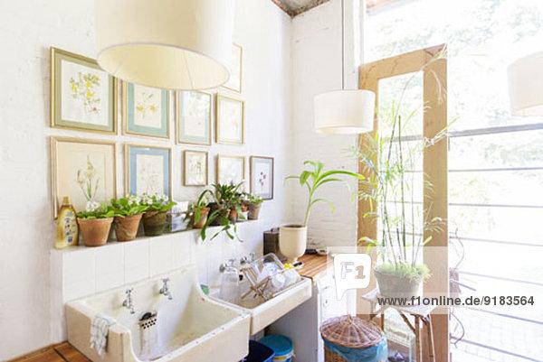 Wandbehänge und Leuchten über rustikaler Küchenspüle