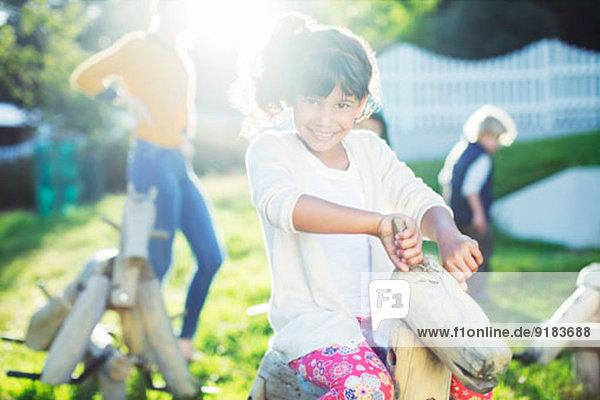 Mädchen lächelnd auf Schaukelpferd im Spielplatz Mädchen lächelnd auf Schaukelpferd im Spielplatz