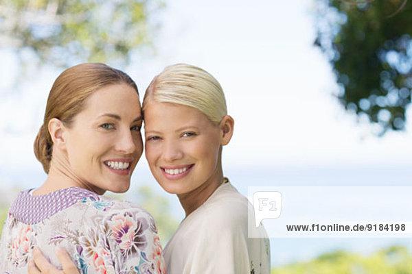 Lächelnde Frauen  die sich drinnen umarmen.