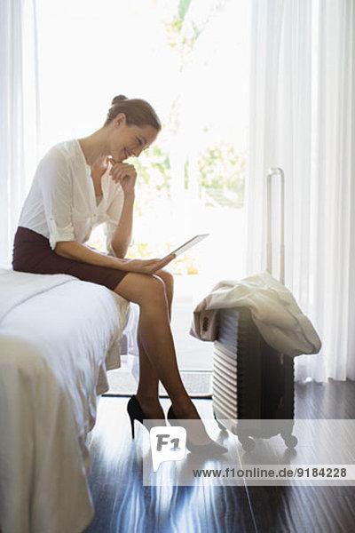 Geschäftsfrau mit digitalem Tablett im Hotelzimmer