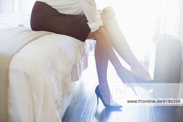 Geschäftsfrau beim Ausziehen der Schuhe im Hotelzimmer