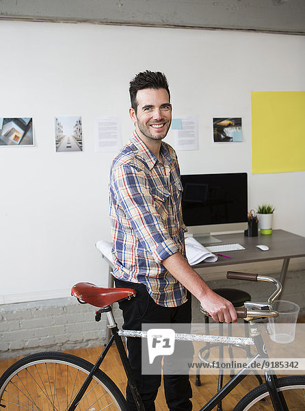 Caucasian architect wheeling bicycle in office