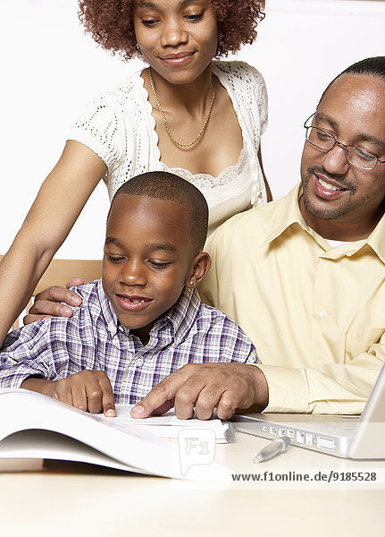 African American parents helping son with homework