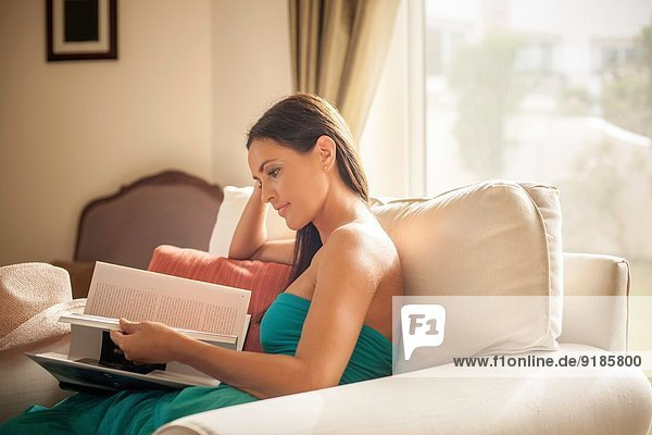 Junge Frau im Sessel sitzend Lesebuch