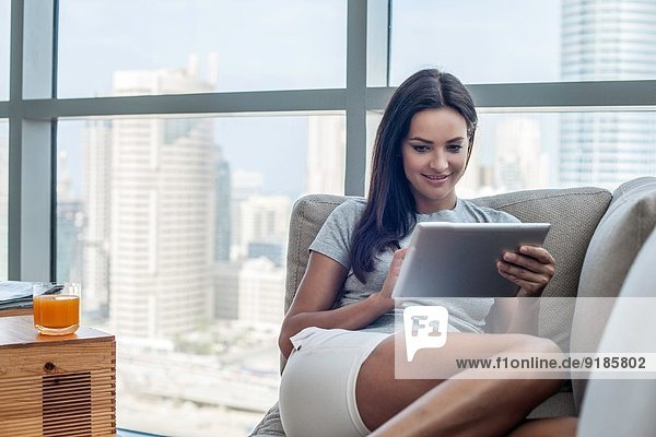 Junge Frau auf dem Sofa liegend mit digitalem Tablett
