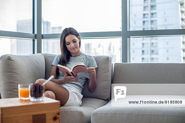 Junge Frau auf Sofa Lesebuch