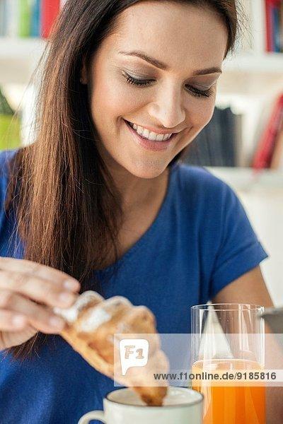 Nahaufnahme einer jungen Frau  die ein Croissant in eine Kaffeetasse taucht.