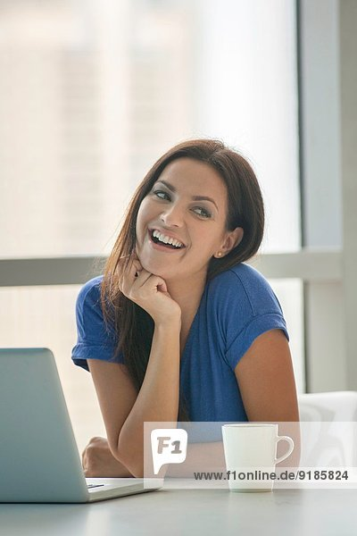 Junge Frau am Tisch mit Laptop und Kaffee