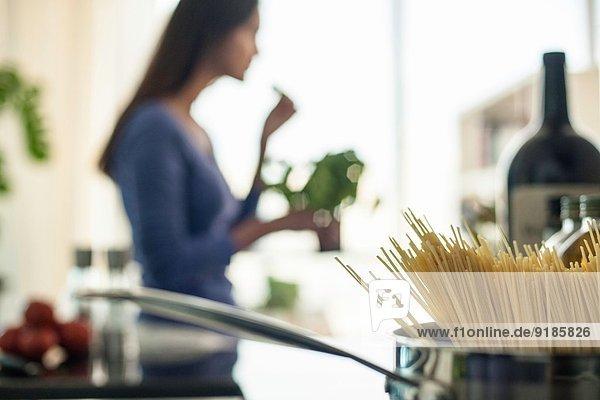 Verschwommenes Bild einer jungen Frau  die in der Küche Essen zubereitet.