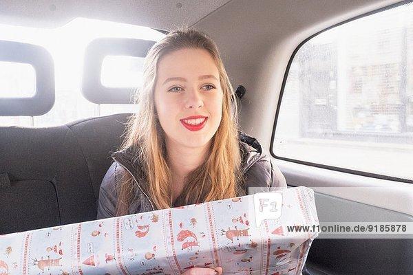 Teenagermädchen auf dem Rücksitz des Fahrerhauses  mit Geschenk