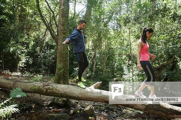 Junge Jogger balancieren auf Baumstamm