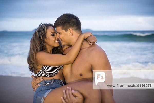 Junger Mann mit Freundin in den Armen am Strand von Ipanema  Rio de Janeiro  Brasilien
