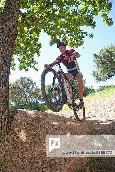 Männlicher Radfahrer  der über den Boden reitet