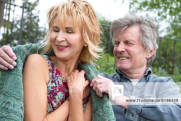 Senior Mann wickelt Frau in warmen Pullover im Park ein