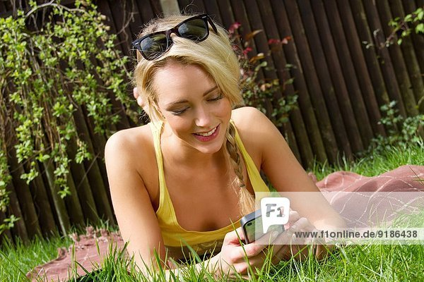 Junge Frau liegt im Garten und liest Texte auf dem Smartphone.