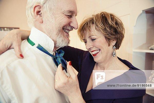 Reife Frau legt Fliege auf älteren Mann