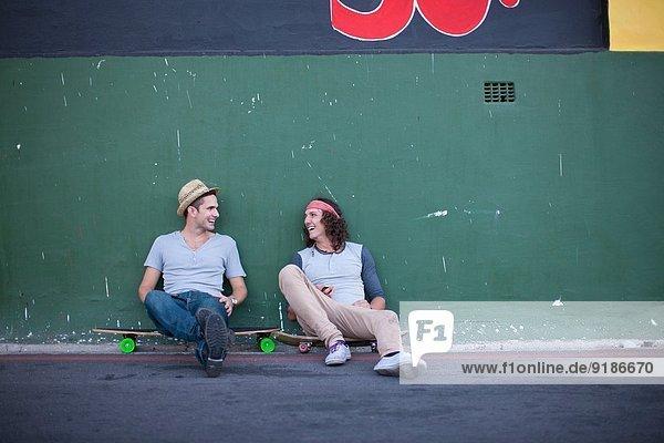 Zwei erwachsene männliche Freunde sitzen auf Skateboards und plaudern.