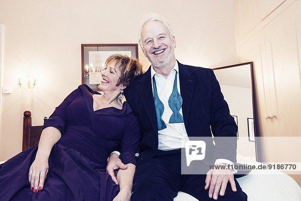 Paar auf dem Bett sitzend  lachend