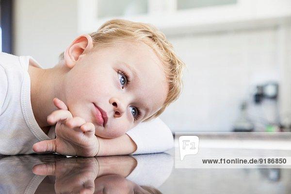 Porträt eines dreijährigen Jungen auf der Küchenbank
