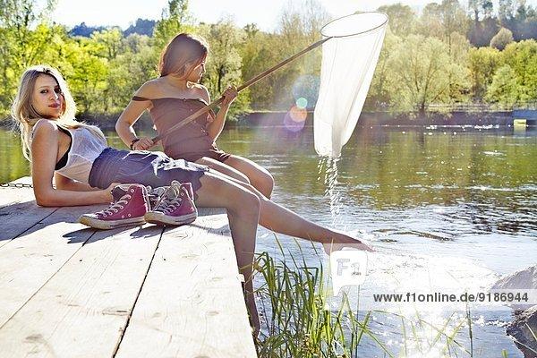 Junge Frauen sitzen am Steg  eine hält ein Fischernetz.