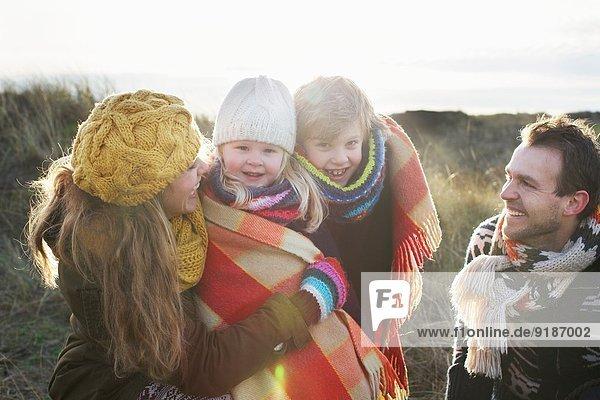 Mittleres erwachsenes Paar in Sanddünen mit Sohn und Tochter in Decke gehüllt