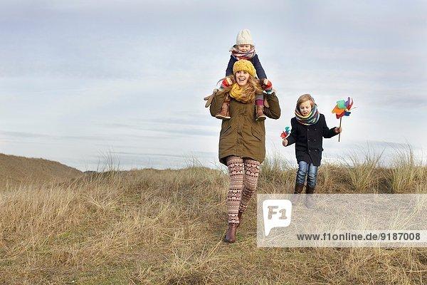 Lächelnde mittlere erwachsene Frau mit Tochter und Sohn an der Küste