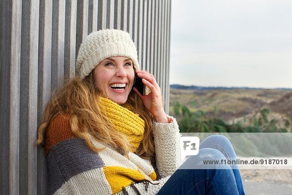 Portrait of mid adult woman chatting on smartphone at coast