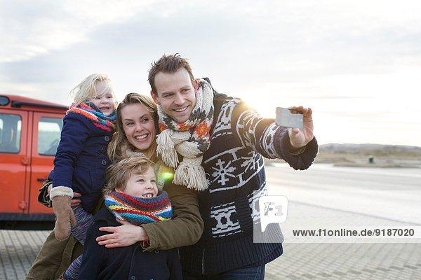 Mittlerer erwachsener Mann  der einen Familien-Selfie auf dem Küstenparkplatz nimmt
