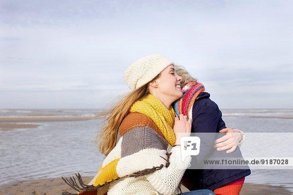 Mittlere erwachsene Frau umarmt Tochter am Strand  Bloemendaal aan Zee  Niederlande