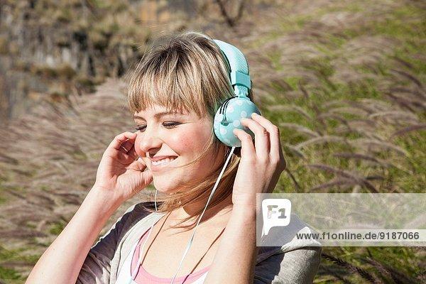 Junge Frau mit geschlossenen Augen hört Kopfhörer im langen Gras