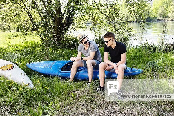 Two young men sitting on a canoe