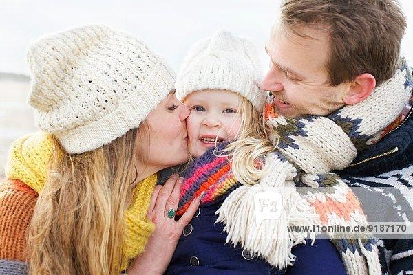 Mittlere erwachsene Eltern küssen ihre Tochter auf die Wange an der Küste.