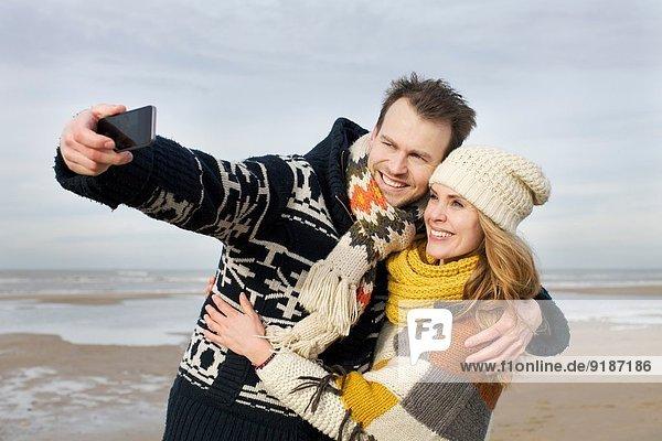Mittleres erwachsenes Paar nimmt Selfie mit Smartphone am Strand  Bloemendaal aan Zee  Niederlande