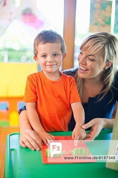Porträt von Jungen und Lehrern im Kindergarten