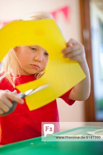 Mädchen beim Ausschneiden von Pappfiguren im Kindergarten