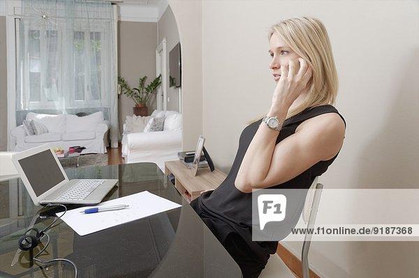Junge Frau beim Plaudern auf dem Smartphone zuhause