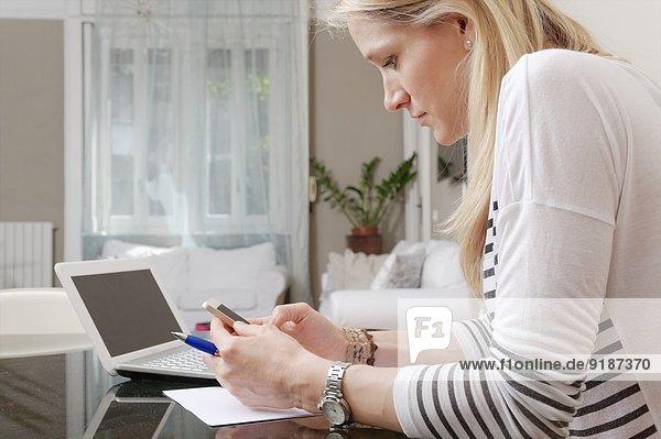 Junge Frau liest Textnachricht auf dem Smartphone zuhause