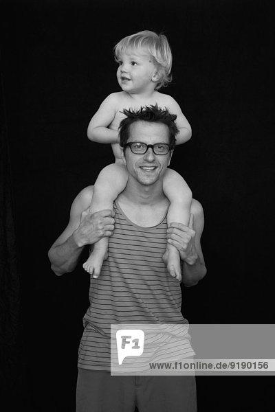 Porträt eines lächelnden Vaters mit Sohn auf den Schultern