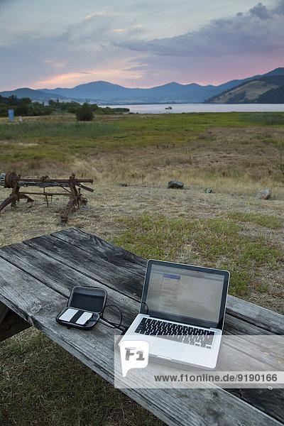 Laptop und Festplatte auf Holztisch im Feld