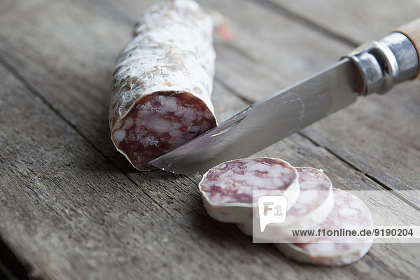Knife slicing sausage on table