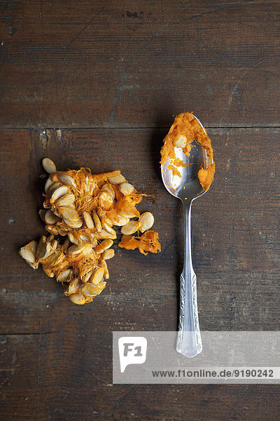 Directly above shot of squash seeds with spoon on table