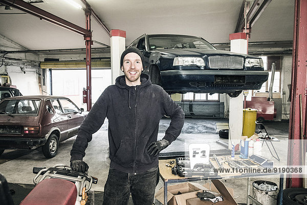 Portrait of confident male auto mechanic standing with hand on hip in repair shop