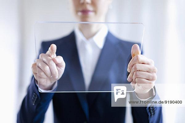 Nahaufnahme der Geschäftsfrau beim Berühren eines leeren  futuristischen digitalen Tabletts