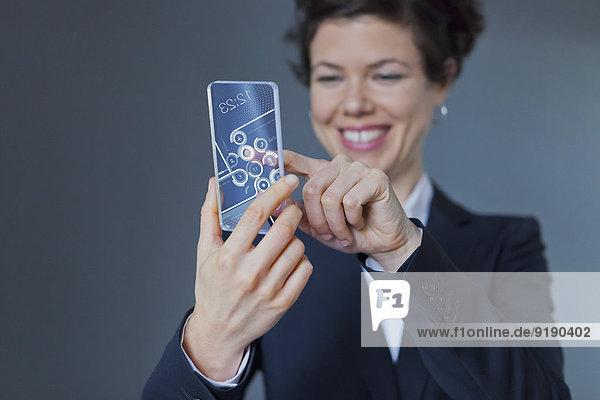 Glückliche Geschäftsfrau Berühren auf modernen transparenten Smart Phone